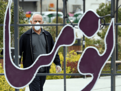 A man wearing a protective face mask and plastic gloves walks along a street in Iran's capital Tehran on March 14, 2020. (Photo by STRINGER / AFP) (Photo by STRINGER/AFP via Getty Images)