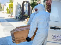 Undertakers wearing a face mask and overalls unload a coffin out of a hearse on March 16, 2020 at the Monumental cemetery of Bergamo, Lombardy, as burials of people who died of the new coronavirus are being conducted at the rythm of one every half hour. (Photo by Piero Cruciatti …
