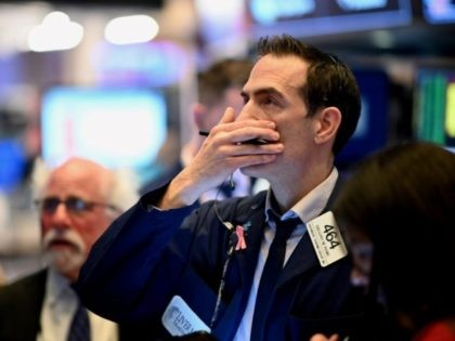 Traders work during the opening bell at the New York Stock Exchange (NYSE) on March 16, 2020 at Wall Street in New York City. - Trading on Wall Street was halted immediately after the opening bell Monday, as stocks posted steep losses following emergency moves by the Federal Reserve to …