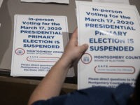 TOPSHOT - County election workers hand out election delayed signs to put up at polling stations in Dayton, Ohio on March 17, 2020 after the primaries were canceled. - Ohio health officials ordered the state's polling stations closed for Tuesday's Democratic primary, as the governor defied a court ruling and …