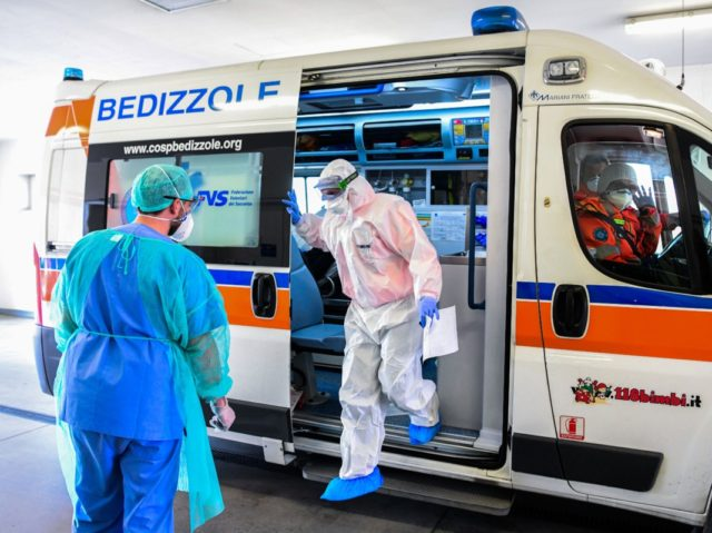A medical worker wearing a face mask brings a patient in an ambulance arriving at the new coronavirus intensive care unit of the Brescia Poliambulanza hospital, Lombardy, on March 17, 2020. (Photo by Piero CRUCIATTI / AFP) (Photo by PIERO CRUCIATTI/AFP via Getty Images)