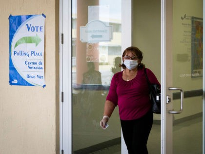 A woman wearing mask and protective gloves leaves after cast her vote during the Florida Democratic primary election at Miami-Dade Public Library Little Havana in Miami, Florida, on March 17, 2020. - Millions of anxious Americans troop to polling stations Tuesday in three states, but not Ohio, as the coronavirus …