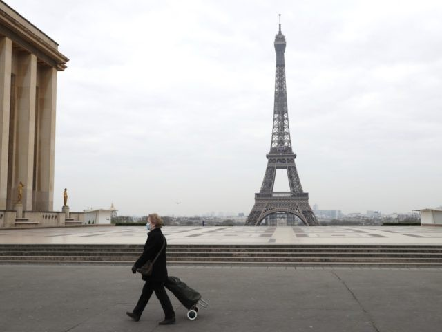 A woman with protective mask walks by the Esplanade du Trocadero square near the Eiffel Tower in Paris, on March 18, 2020 in Paris as a strict lockdown comes into in effect in France to stop the spread of COVID-19, caused by the novel coronavirus. - A strict lockdown requiring …