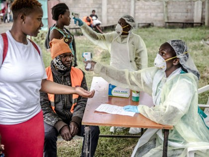 Health personnel measure the temperature of a visitor at the entrance of the Mbagathi Hospital in Nairobi, Kenya on March 18, 2020. - The Government of Kenya confirmed new positive cases of COVID-19 coronavirus on March 18, 2020, bringing the total official number of cases in the East African country …