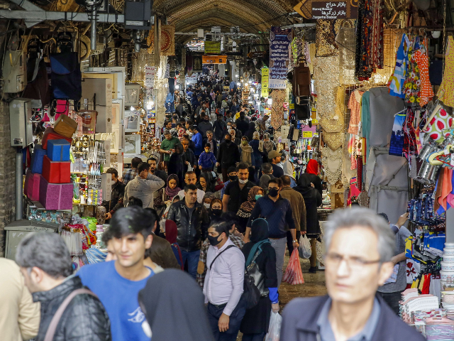 Iranians, some wearing protective masks, gather inside the capital Tehran's grand bazaar, during the Covid-19 coronavirus pandemic crises, on March 18, 2020. - Iran said its novel coronavirus death toll surpassed 1,000 today as President Hassan Rouhani defended the response of his administration, which has yet to impose a lockdown. …