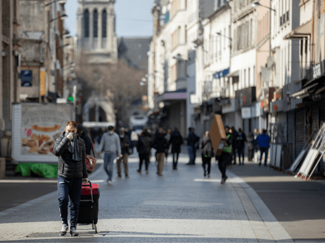 People walk in a shopping street of Saint-Denis, near Paris on March 18, 2020, after a strict lockdown came into effect in France to stop the spread of the COVID-19, caused by the novel coronavirus. - A strict lockdown requiring most people in France to remain at home came into …