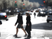 A couple wearing masks cross a street in manhattan on March 18, 2020 in New York City. - The number of global coronavirus infections shot past 200,000 on March 18, 2020, as governments across Europe, North America and Asia rolled out tough measures to put the brakes on the ferocious …