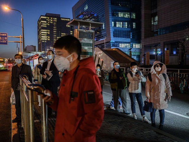 BEIJING, CHINA - MARCH 20: Chinese commuters wear protective masks as they line up in a staggered formation while waiting for a bus at the end of the work day on March 20, 2020 in Beijing, China. With the pandemic hitting hard across the world, China recorded its first day …