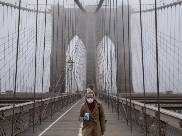 NEW YORK, NY - MARCH 20: A woman wearing a mask walks the Brooklyn Bridge in the midst of the coronavirus (COVID-19) outbreak on March 20, 2020 in New York City. The economic situation in the city continued to decline as New York Gov Andrew Cuomo ordered all nonessential businesses …