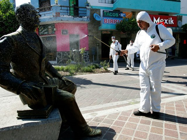 Workers wearing a protective suits sprays disinfectant during a campaign to sanitize public spaces as a preventive measure against the spread of the new coronavirus, COVID-19, in Guadalajara, Mexico, on March 20, 2020. (Photo by ULISES RUIZ / AFP)