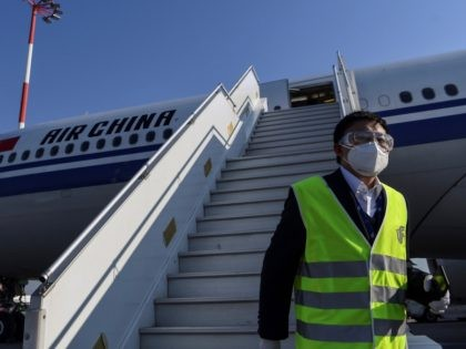 A member of staff, wearing a facemask for protective measures, disembarks from an Air China airbus carrying 500.000 protective masks at the Athens international airport, on March 21, 2020, as part of aid measures from China, to help the country and Europe to fight against the spread of the Covid-19, …