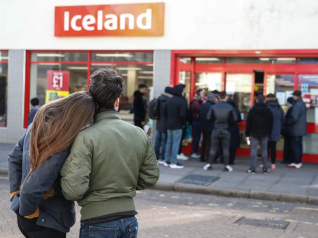 LONDON, ENGLAND - MARCH 21: People line up outside an Iceland supermarket on Roman Road in Bow on March 21, 2020 in London, England. Londoners are feeling the impact of shutdowns due to Coronavirus. Coronavirus (COVID-19) has spread to at least 186 countries, claiming over 11,000 lives and infecting more …