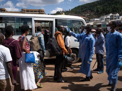 A staff of the Rwanda Biomedical Center (RBC) screens passengers at a bus station after the government suspended all unnecessary movements for two weeks to curb the spread of COVID-19 Coronavirus in Kigali, Rwanda, on March 22, 2020. - African countries have been among the last to be hit by …