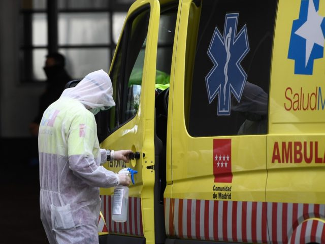 A paramedic disinfects the door handle of an ambulance outside La Paz hospital in Madrid on March 23, 2020 amid a national lockdown to fight the spread of the COVID-19 coronavirus. - The coronavirus death toll in Spain surged to 2,182 after 462 people died within 24 hours, the health …