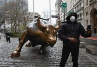 A man wearing a face mask takes a selfie at the Charging Bull statue on March 23, 2020 near the New Stock Exchange in New York City. - Wall Street fell early March 23, 2020 as Congress wrangled over a massive stimulus package while the Federal Reserve unveiled new emergency …