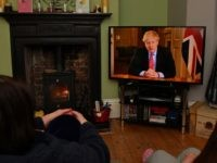 Members of a family listen as Britain's Prime Minister Boris Johnson makes a televised address to the nation from inside 10 Downing Street in London, with the latest instructions to stay at home to help contain the Covid-19 pandemic, from a house in Liverpool, north west England on March 23, …