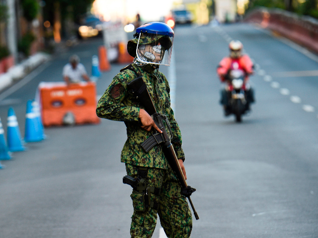 A policeman wearing a facemask stands guard at a checkpoint after the government imposed an enhanced quarantine as a preventive measure against the COVID-19 novel coronavirus in Manila on March 25, 2020. (Photo by Ted ALJIBE / AFP) (Photo by TED ALJIBE/AFP via Getty Images)