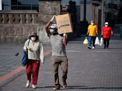 """People carry provisions as they walk along the historic centre of Quito on March 25, 2020 during the novel coronavirus, COVID-19, pandemic. - President Lenin Moreno on Tuesday called out Ecuadorans who flouted isolation measures -- including a daily curfew -- saying their actions amounted to """"terrorism."""" (Photo by Rodrigo …"""