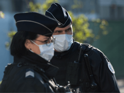 Police officers wearing a face mask stand guard in front of the Nantes railway station, on March 26, 2020 in Nantes, following the arrival of a medicalized TGV high-speed train carrying patients infected with the covid-19 from eastern France, where hospitals are overwhelmed. (Photo by Loic VENANCE / AFP) (Photo …