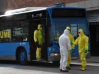 Members of Spanish Military Emergencies Unit (UME) wearing protective suits stand outside a bus used to transport patients from the San Carlos Clinic Hospital to a temporary hospital set-up for coronavirus patients at the Ifema convention and exhibition center in Madrid, on March 29, 2020. - Spain confirmed another 838 …