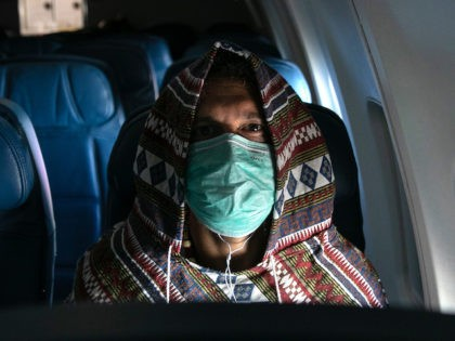 NEW YORK, NY - MARCH 15: Adam Carver, 38, wears a mask to protect against coronavirus while on a nearly empty Delta flight from Seattle-Tacoma International Airport o JFK on March 15, 2020 near New York City. Carver, a Brooklyn-based tech entrepreneur, was returning from an extended trip to Asia …