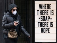 LONDON, ENGLAND - MARCH 17: A woman wearing a protective mask walks past a sign in a cosmetic shop window on March 17, 2020 in London, England. Boris Johnson held the first of his public daily briefing on the Coronavirus outbreak yesterday and told the public to avoid theatres, going …