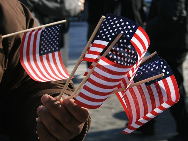 Man holding miniature Amercian flags.