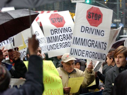 NEW YORK - APRIL 13: Pedestrians walk by a demonstration by immigrants and community leaders protesting the New York State Department of Motor Vehicles (DMV) policies that deny driver's licenses and state ID's to hundreds of thousands of immigrant New Yorkers April 13, 2004 in front of the DMV on …
