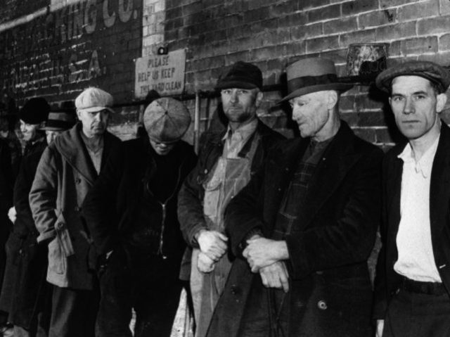 April 1940: A line of men queuing for a meal outside the city mission in Dubuque, Iowa. (Photo by John Vachon/Library Of Congress/Getty Images)