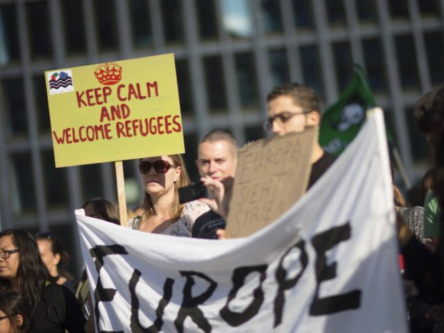 Partcipant of a pro-migrants demonstration holds a sign reading 'Keep calm and welcome refugees' at Potsdamer Platz in Berlin on September 12, 2015. Tens of thousands were due to rally in European capitals Saturday in support of migrants as Hungary's populist prime minister called for a giant aid package for …