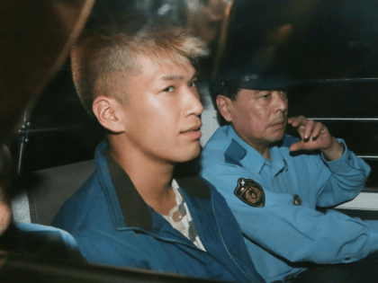 Murder suspect Satoshi Uematsu (L) sits in the back seat of a police vehicle as he returns to the Tsukui police station in Sagamihara, Kanagawa prefecture on July 27, 2016. A Japanese man who admitted murdering 19 people at a centre for the mentally disabled grinned at news cameras on …