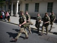 TOPSHOT - British Army soldiers are led by a police officer into Buckingham Palace in central London on May 24, 2017. - Britain deployed soldiers to key sites Wednesday and raised its terror alert to the maximum after the Manchester suicide bombing by Salman Abedi, reportedly a Briton of Libyan …