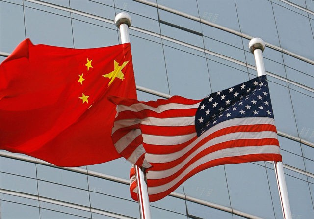 """Beijing, CHINA: A US and a Chinese flag wave outside a commercial building in Beijing, 09 July 2007. US Secretary of State Condoleezza Rice 06 July 2007 accused China of flouting the rules of global trade in its headlong economic expansion as the US administration """"has not been hesitant"""" to …"""