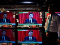 An electronics shop employee in Hong Kong on October 18, 2017 looks at television sets showing a news report on China's President Xi Jinping's speech at the opening session of the Chinese Communist Party's five-yearly Congress at the Great Hall of the People in Beijing. President Xi Jinping declared China …