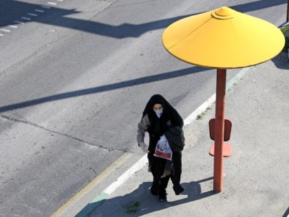 An Iranian pedestrian walks while wearing a protective mask in Tehran on March 10, 2020 amid the spread of coronavirus in the country. - Iran today reported 54 new deaths from the novel coronavirus in the past 24 hours, the highest single-day toll since the start of the country's outbreak. …