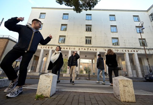 "Students walk by Rome's ""Giulio Cesare"" secondary classic school on March 5, 2020 after Italy closed all schools and universities until March 15 to help combat the spread of the novel coronavirus crisis. - The government decision was announced moments after health officials said the death toll from COVID-19 had …"