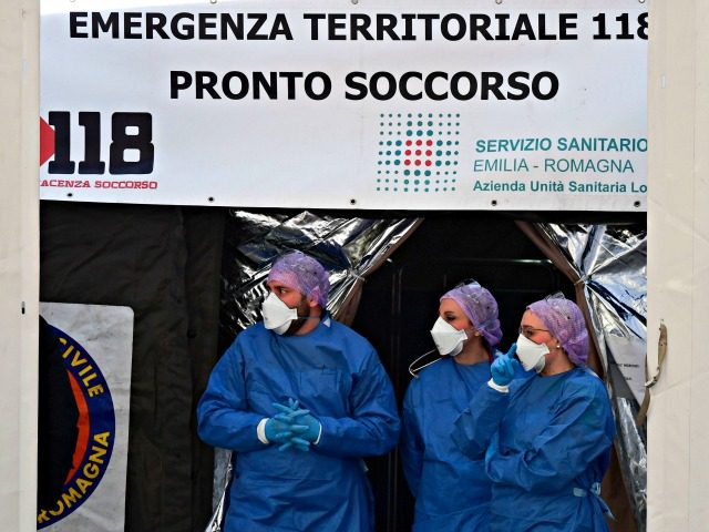 Medical staff wait outside a sanitary tent installed in Piacenza next to the hospital on February 26, 2020. - Italy saw a fresh jump in the number of cases of the new coronavirus on February 26, 2020 with another death also reported to bring the total to 12 and 374 …