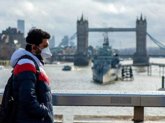 LONDON, ENGLAND - MARCH 14: A man wearing a face mask walks over London Bridge, with Tower Bridge seen behind, as the outbreak of coronavirus intensifies on March 14, 2020 in London, England. Many Londoners and tourists are continuing they daily activities whilst mass gatherings could be banned in the …