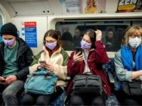 Commuters wear masks as a precaution whilst travelling on a London Underground metro train in the morning in central London on March 18, 2020 as people take precautions amid the coronavirus outbreak. - The British government will on Wednesday unveil a raft of emergency powers to deal with the coronavirus …