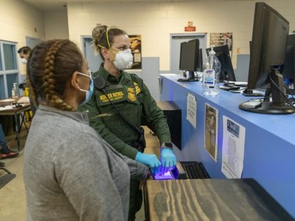 A U.S. Border Patrol agent conducts a biometric background investigation on an illegal alien. (Photo: U.S. Border Patrol/San Diego Sector)