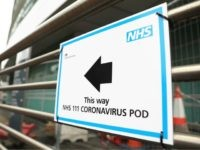A sign directs directs patients to an NHS 111 Coronavirus Pod testing service area for COVID-19 assessment at University College Hospital in London on March 5, 2020. - The number of confirmed cases of novel coronavirus COVID-19 in the UK rose to 85 on March 4, with fears over the …