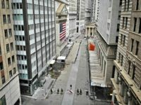A lone pedestrian wearing a protective mask walks past the New York Stock Exchange as COVID-19 concerns empty a typically bustling downtown area, Saturday, March 21, 2020, in New York. New York Gov. Andrew Cuomo announced sweeping orders Friday that will severely restrict gatherings of any size for the state's …