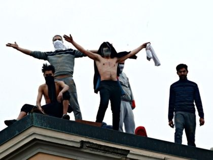 Inmates stand on the roof of the San Vittore prison to protest after restrictions that were imposed on family visits to prevent coronavirus transmissions, in Milan, Italy, Monday, March 9, 2020. Italian penitentiary police say six inmates protesting virus containment measures at the northern Italian prison of Modena have died …