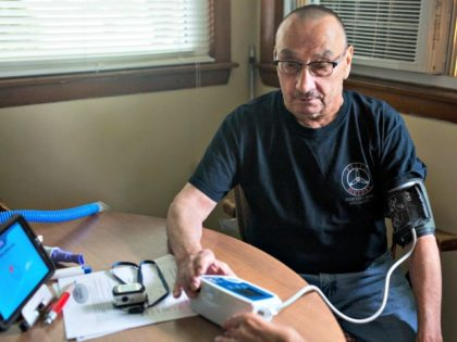 A man measures his vitals and sends the data electronically to nurses. Photo: Brianna Soukup/Portland Portland Press Herald/Getty Images