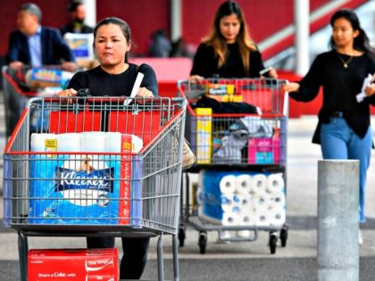 People leave a Costco warehouse with rolls of toilet paper amongst their groceries in Melbourne on March 5, 2020. – COVID-19 coronavirus fears have triggered runs on several products, including hand sanitisers and face masks, with images of shoppers stacking trolleys with toilet rolls spreading on social media. (Photo by …