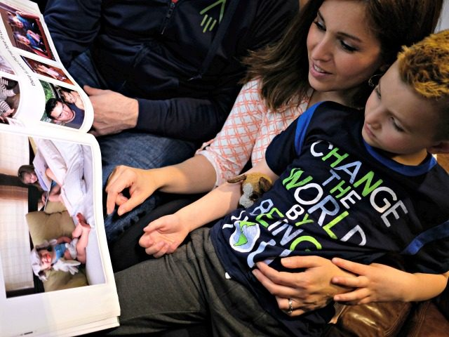 Seven-year-old transgender boy Jacob Lemay and his parents Joe and Mimi look at their family photo before his transition at their home in Melrose, Massachusetts, on May 9, 2017. For months in the Lemay home, the same phrase was repeated over and over by their troubled young child, barely more …