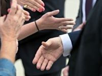 President Donald Trump, bottom right hand, shakes hands with supporters upon arrival at the Orlando Sanford International Airport, Monday, March 9, 2020 in Orlando, Fla. (AP Photo/Alex Brandon)