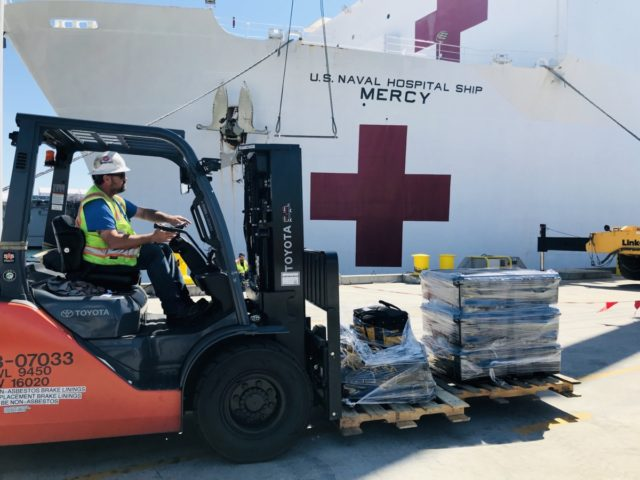 SAN DIEGO, CA - MARCH 21: Steve King, a Naval Facilities Engineering Command Southwest forklift driver, prepares to deliver pallets during a supply load aboard the Military Sealift Command hospital ship USNS Mercy (T-AH 19) at Naval Base San Diego, March 21, 2020. Mercy is preparing to deploy in support …