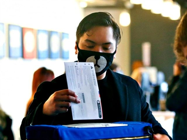 © Jason Redmond/AFP via Getty Images Matthew Guerrero, 22, of Des Moines, Washington wears a bear mask as he drops off his presidential primary mail-in ballot in person at King County Elections in Renton, Washington, March 10, 2020.