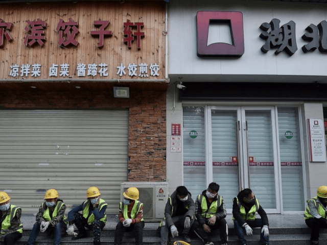"In this Sunday, Feb. 23, 2020, photo, workers take a rest near the closed restaurant and bank in Wuhan in central China's Hubei province. Warning that China's virus epidemic is ""still grim and complex,"" President Xi Jinping called Sunday for more efforts to stop the outbreak, revive industry and prevent …"